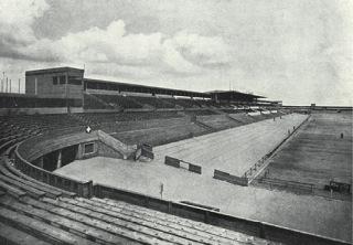 Pohled z jižní tribuny na hlavní tribunu a vstupní bránu (zdroj: [1], str. 45)