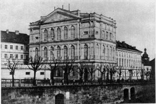 Prozatímní divadlo na vizitce  Františka  Fridricha  z  poloviny  šedesátých  let 19. století, fotografované z řetězového mostu. V Prozatímním divadle, spojeném s Národním divadlem spolu se sousedním domem v jeden celek,  se hrálo naposledy 18. dubna 1883