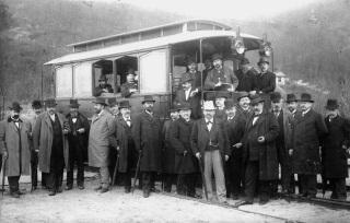Uplatnit elektrickou energii v dopravě se snažil František Křižík rovněž na železnici. Pro svou pouliční elektrickou dráhu Praha – Libeň – Vysočany zakoupil v roce 1898 ve Vídni dva starší (původně americké) akumulátorové vozy, z nichž jeden upravil pro provoz na železničních kolejích. K pokusům vybral železniční trať Nusle – Modřany – Měchenice. K dobíjení akumulátorů zřídil dvě nabíjecí stanice – v Nuselských topírnách a na Zbraslavi. Dobíjení akumulátorů trvalo 30 min. První jízdu uskutečnil Křižík 6. března 1899.