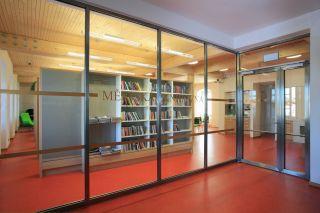 Knihovna ve 2.NP, pohled přes požární prosklenou stěnu z podesty schodiště