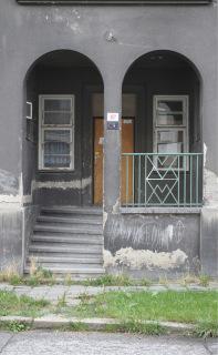 Obr. 12 Detail domovního vstupu s dochovaným kovovým zábradlím s motivem V a W – tj. Vítkovice či též Witkowitz jako odkaz na Vítkovické železárny (foto: Martin Strakoš, srpen 2010)