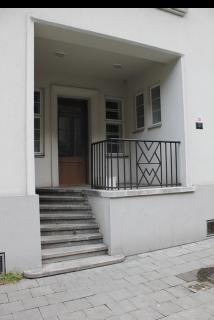 Obr. 13 Detail domovního vstupu s dochovaným kovovým zábradlím s motivem V a W – tj. Vítkovice či též Witkowitz jako odkaz na Vítkovické železárny (foto: Martin Strakoš, srpen 2010)