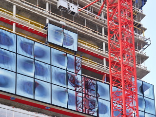 Obr. 21 Osazování skleněných panelů pláště budovy (únor 2010)