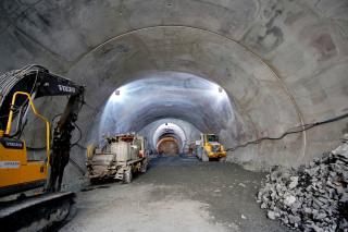 Finální železobetonové ostění horního staničního tunelu. V pozadí je začátek ražby traťového tunelu.