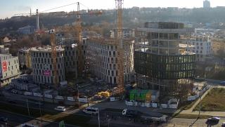 Téměř kompletní nosná konstrukce obou budov a počátek montáže rastrové fasády na menší budově B