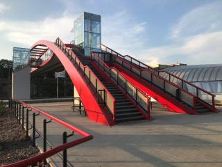 Boční pohled na veřejný výtah, umístěný mezi ramena schodiště. Druhý výtah je bokem od lávky na druhém nástupišti.