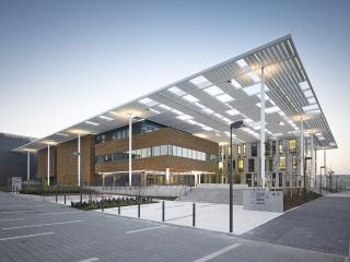 Uprostřed je multifunkční budova s fasádním obkladem ze sibiřského modřínu a vláknocementových desek. Kancelářská budova vpravo a laserová hala vlevo vzadu mají obklad z hliníkových sendvičových desek bond v odlišném formátu a barvě.