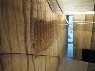 Původní materiály se využily zejména ve společných prostorech jejich vložením do pohledového monolitického železobetonu