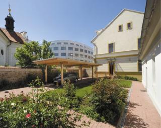 Budova je nově více propojena se zahradou a dvorem, kde vznikl nový přístřešek nejen pro parkování auta, ale především pro pořádání venkovních setkání