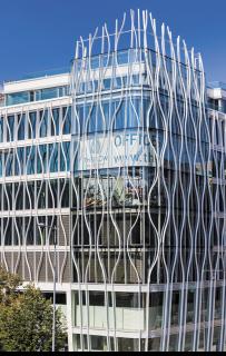 V nároží budovy je předsazena zakřivená fasáda, která je tvořena obloukovými moduly včetně obloukových skel, zapuštěná fasáda je opět rovná