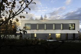 Kompozice  umístění oken a plasticita fasády rozehrává dynamiku, navíc přilehlý les hází stíny na fasádu při západu slunce