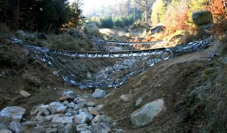 Obr. 11 Vybudované flexibilní bariéry VX firmy GEOBRUGG v levé větvi strže S1, pohled ze silnice proti svahu