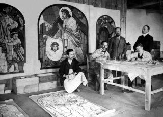 Obr. 03 Dobová fotografie z ateliéru Rako asi před rokem 1930. Mistr Jano Koehler stojí uprostřed, na zdi jsou jeho kartony. Keramici řežou segmenty a nanášejí barevné glazury
