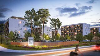 Pohľad na totem v popredí bytových domov v mieste príjazdu k 1. etape projektu