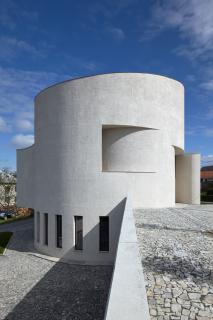 Válcová hmota kostela s konvexními a konkávními prolomeními povrchu. Součástí opěrné zdi v popředí mělo být podle původního projektu i schodiště propojující obě úrovně venkovních prostranství
